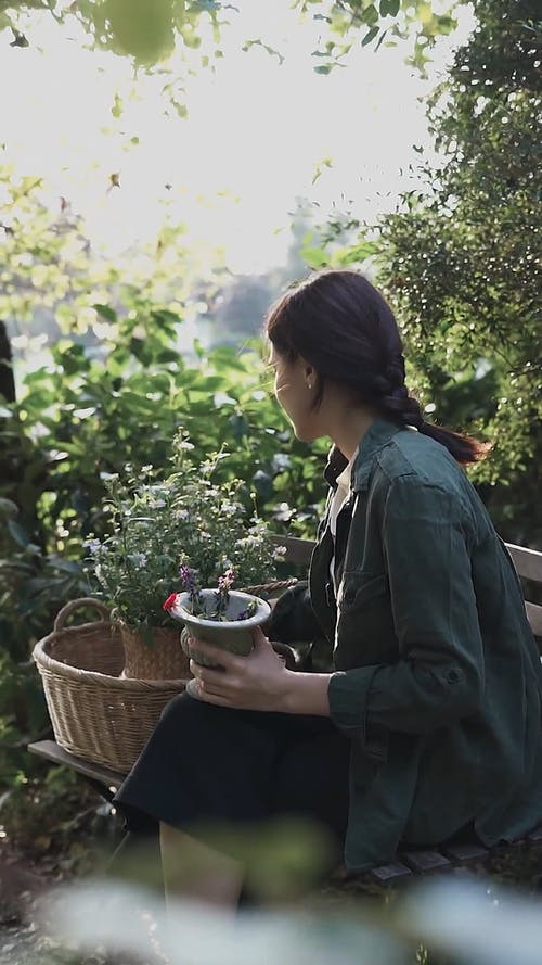 A Woman Looking at the Potted Plant while Sitting