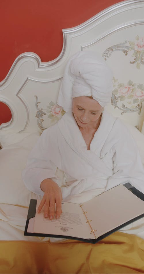 An Elderly Woman in a Bath Robe and Head Towel Reading in Bed