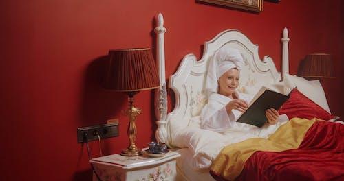 An Elderly Woman Reading a Hotel Guest Directory Binder