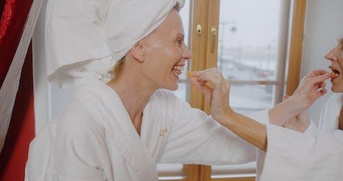 Elderly Women Feeding Each Other Tangerines