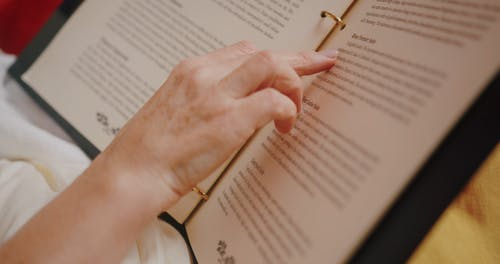 A Person Reading a Hotel Guest Directory Binder