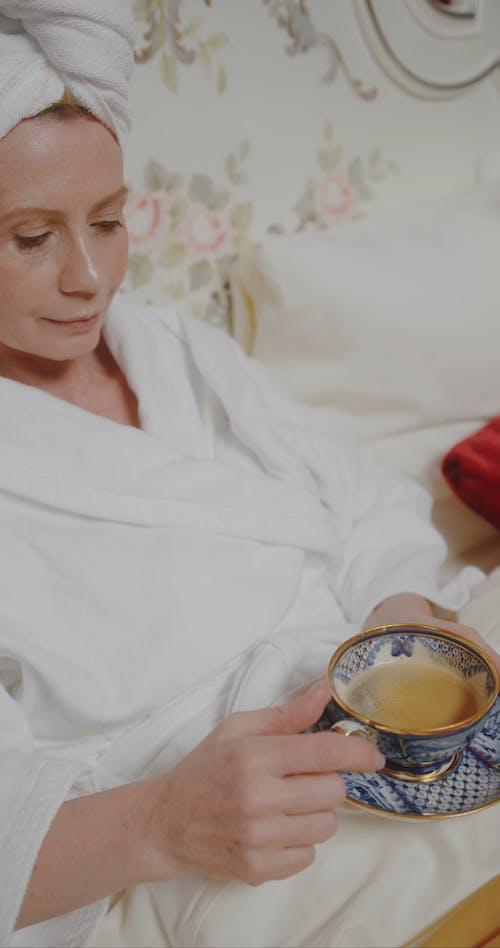 Woman in Bathrobe Drinking Bed Tea