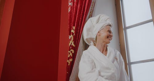 An Elderly Woman in a Head Towel and Bathrobe Smiling by a Window