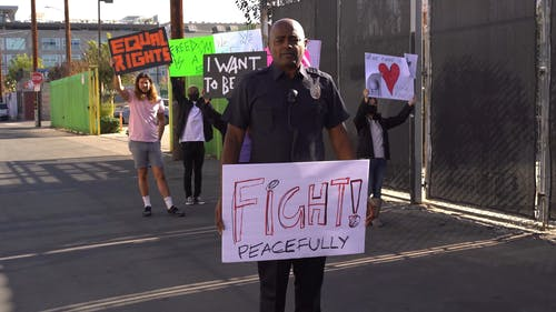 Police Officer Holding a Sign in a Protest