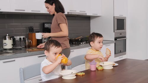 A Mother Making  Coffee and Drinking it While Her Twin Sons are Eating