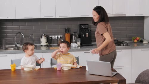 A Mother Cleaning the Hands of Her Son in the Kitchen