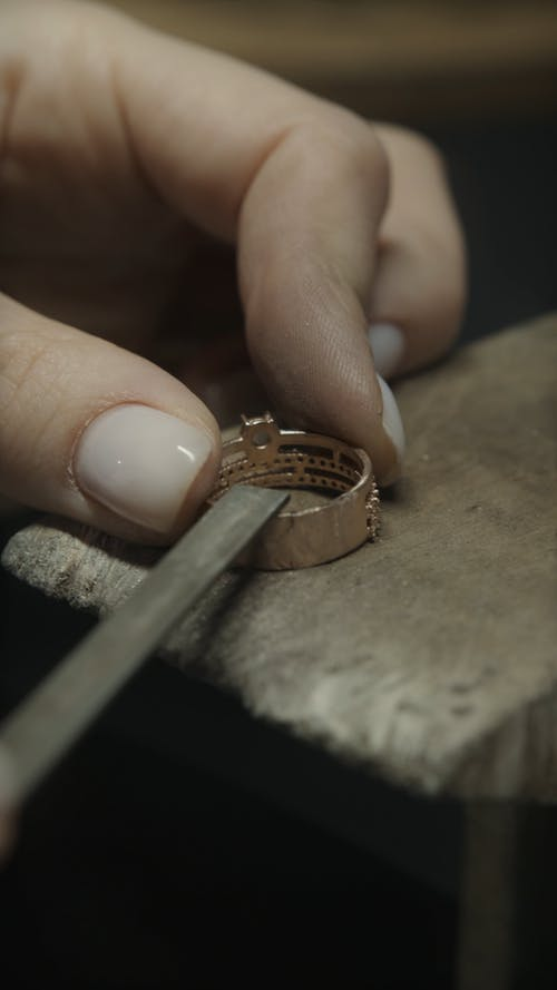 Close Up View of a Person Smoothing a Gold Ring