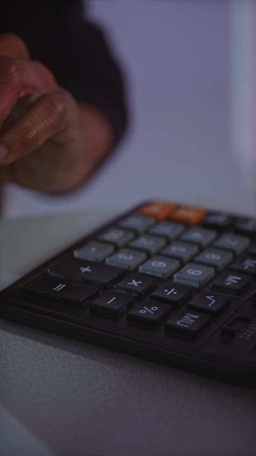A Person Using a Calculator and Typing