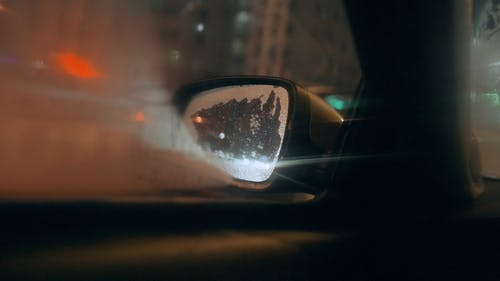 View of City Traffic at Night through Car's Side View Mirror