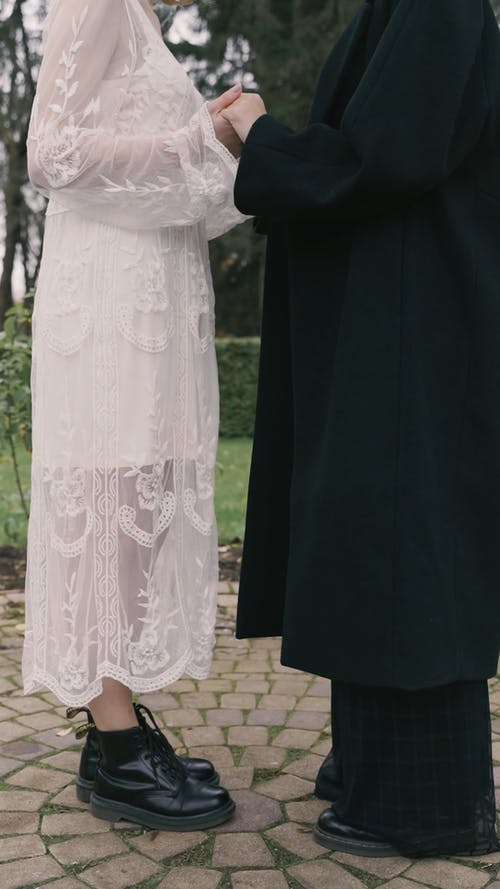 Couple Standing and Holding Hands While Facing Each Other