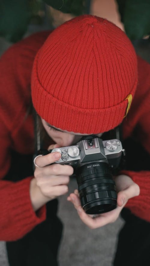 A Woman Wearing Red Bonnet and Sweater Looking Through Camera Lens