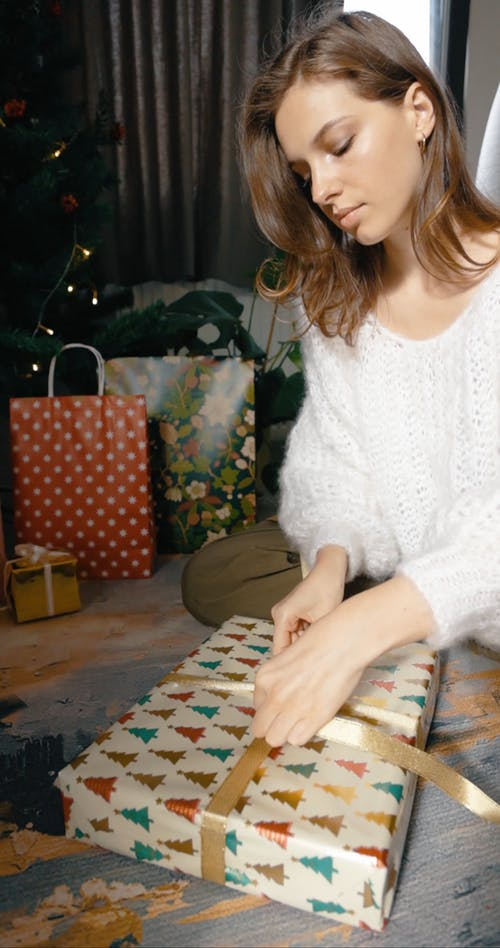 Woman Decorating Gift Box With A Ribbon