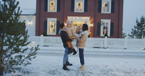 Family Standing Outside their House on Christmas Eve