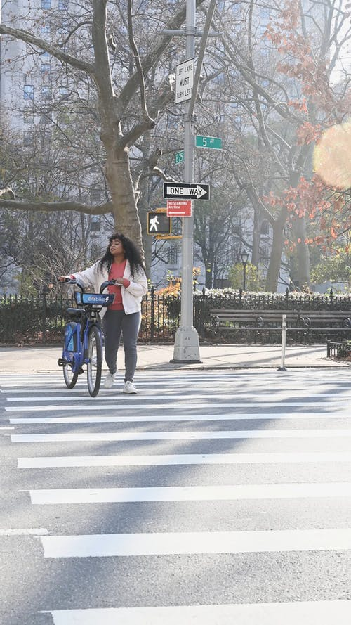 Woman Crossing the Street with a Bike