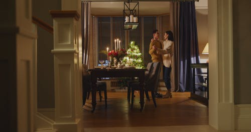 Couple Dancing On Dining Room While Being Observed