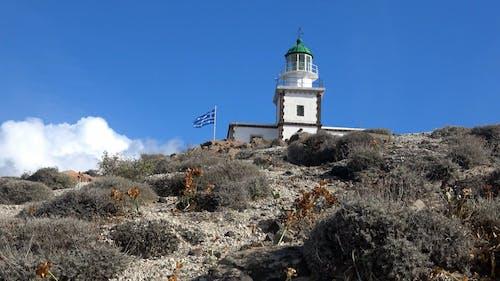 A Flag Waving beside a Lighthouse