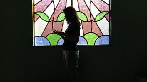 Silhouette of a Woman Texting Behind a Window