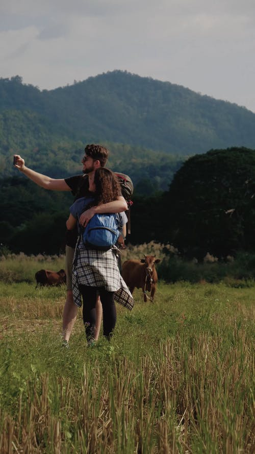 Backpacker Couple Hugging and Making Video of the Surroundings