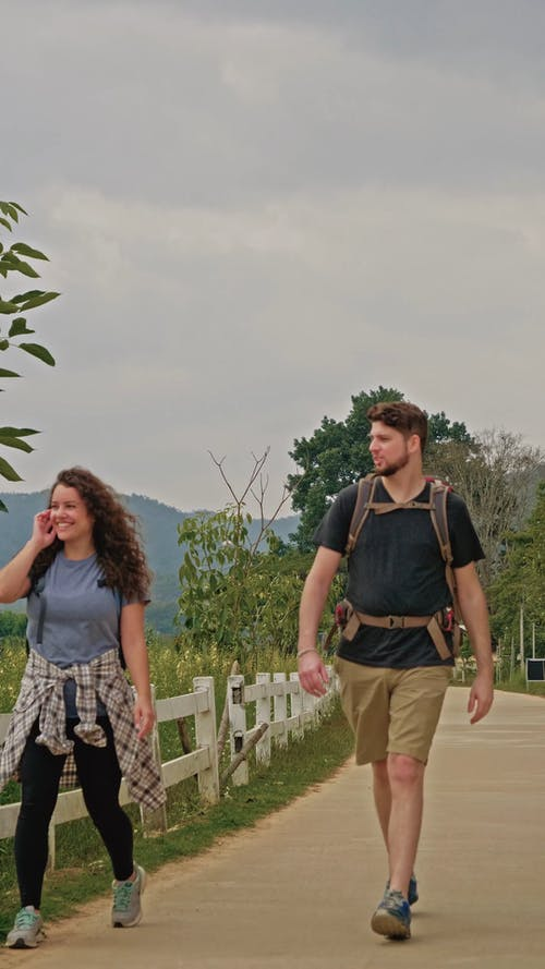 A Backpacker Couple on a Walkway at Countryside
