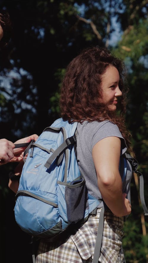 Man Helping his Girlfriend to Fasten her Backpack