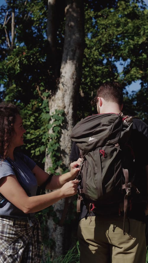 Woman Helping her Boyfriend to Fasten his Backpack