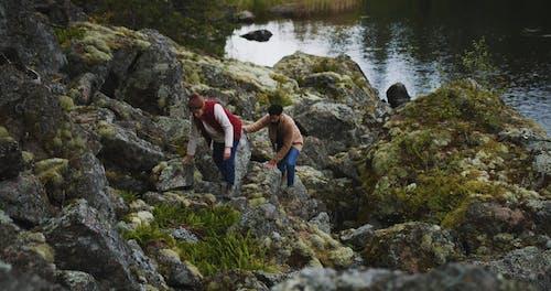 Couple Climbing Rocks In The Lake Shore