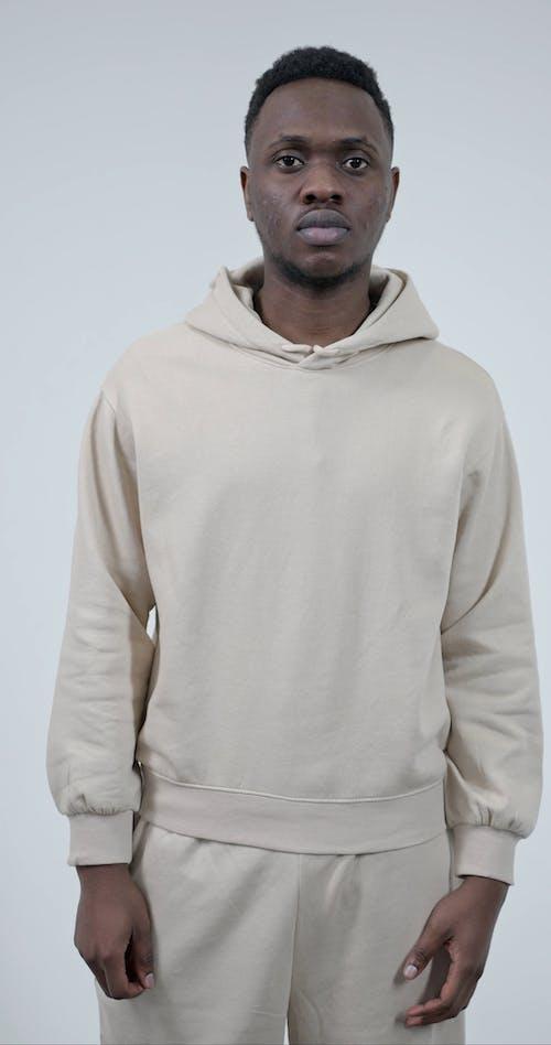 Man In Beige Sweatsuit Posing On Camera