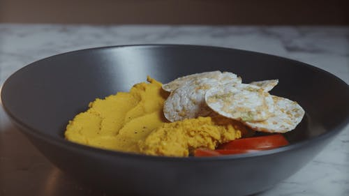 A Person Sprinkling Paprika on a Meal