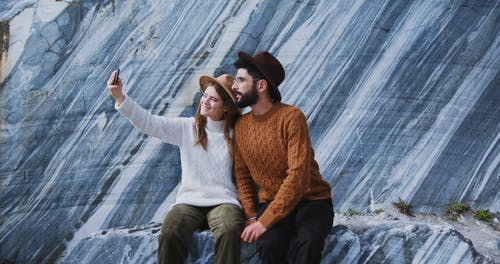 A Couple Sitting while Taking a Picture