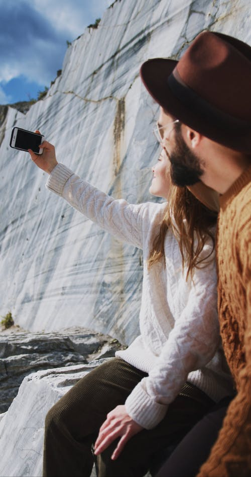 Man and Woman Taking a Selfie Using a Phone