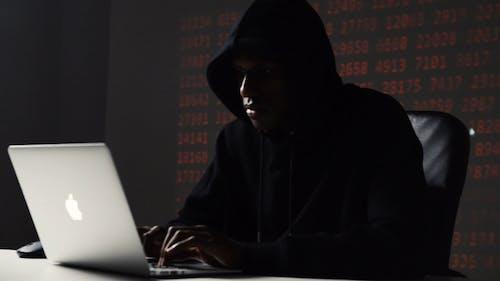 A Man Hacking on a Laptop