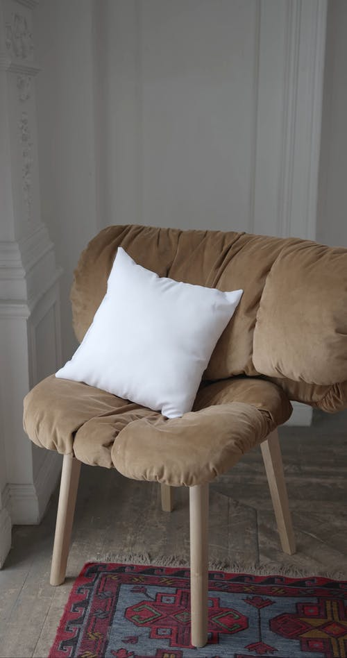 Brown Chair with White Throw Pillow