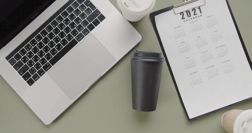 Coffee Mugs Placed in Between of laptop and Calendar