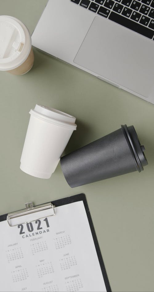 A Work Desk Stuffed with Laptop Calendar and Coffee Cups