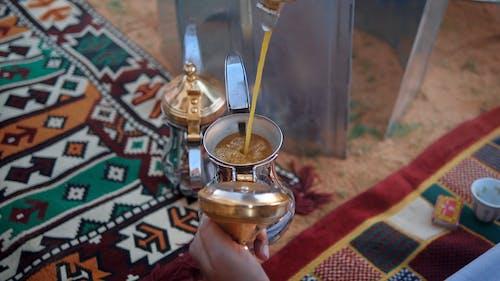 Person Pouring Coffee into Dallah