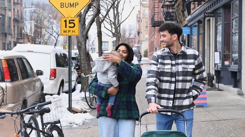 Married Couple Walking on the Street with their Baby while Snowing