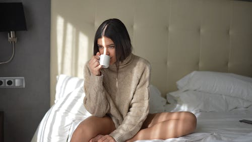 A Woman Drinking Coffee while Sitting on a Bed
