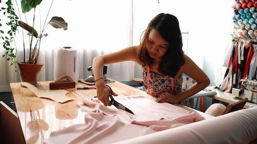 A Woman Cutting a Fabric