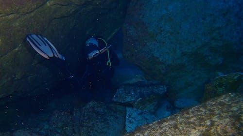 A Scuba Diver Navigating Through Underwater Rocks