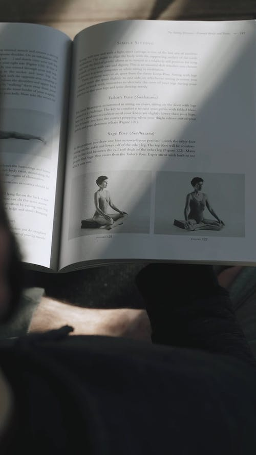 Person Reading More About Yoga through Book