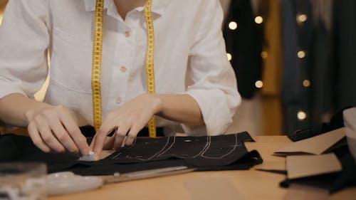 A Female Fashion Designer Marking Garment