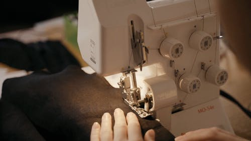 A Woman Stitching the Hem of a Cloth with a Sewing Machine
