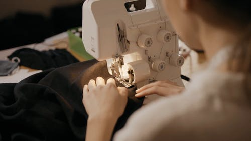 A Woman Stitching a Cloth with a Sewing Machine