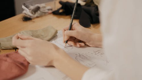 A Woman Sketching a Designer Suit