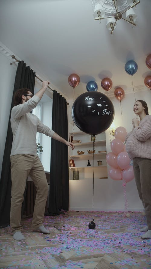 Man Popping Balloon at Gender Reveal Party