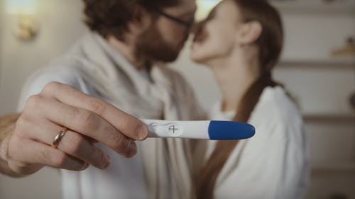 Man Holding Up Pregancy Test While Kissing Wife