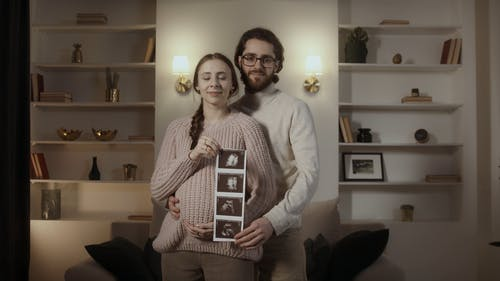 Couple Posing and Holding Up Sonogram
