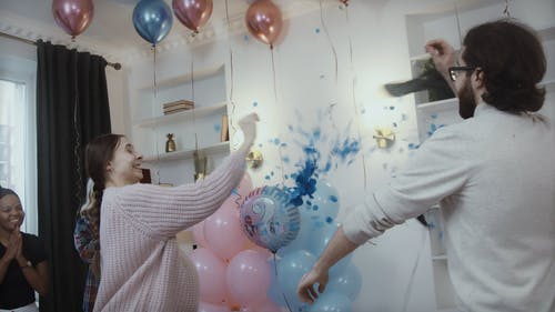 Man and Woman Popping Balloon at Gender Reveal Party