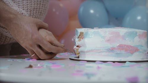 Couple Holding Up Slice of Cake with Pink Filling