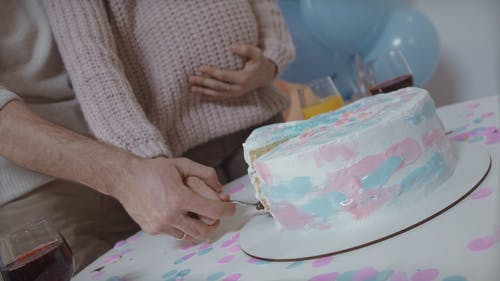 Couple Holding Up Slice of Cake with Blue Filling